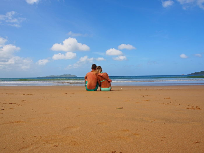 Rear View Of Couple Sitting On Shore At Beach Against Blue Sky