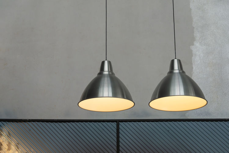 Low angle view of illuminated light bulb hanging on wall