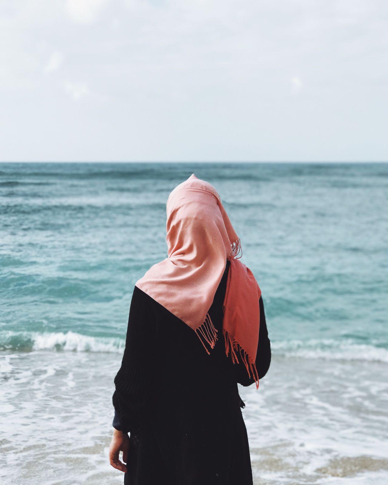 Mid adult woman on beach against sky