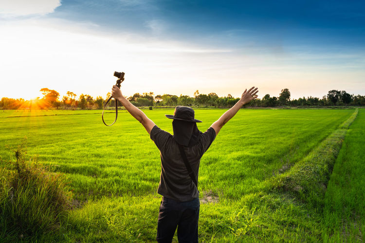 Field One Person Land Sky Real People Grass Standing Plant Green Color Human Arm Beauty In Nature Landscape Leisure Activity Growth Three Quarter Length Nature Environment Arms Raised Lifestyles Limb Outdoors