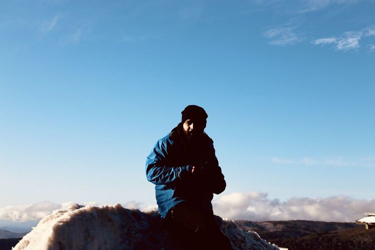 Portrait of man wearing warm clothing while standing against blue sky