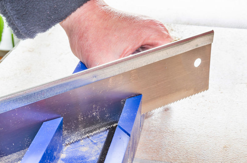 Cropped image of man cutting metal with saw in workshop