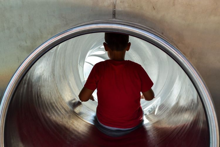 Rear view of boy sitting in slide at playground