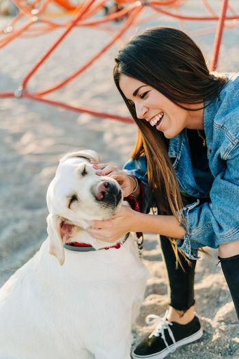 Cheerful woman petting dog at playground during sunset