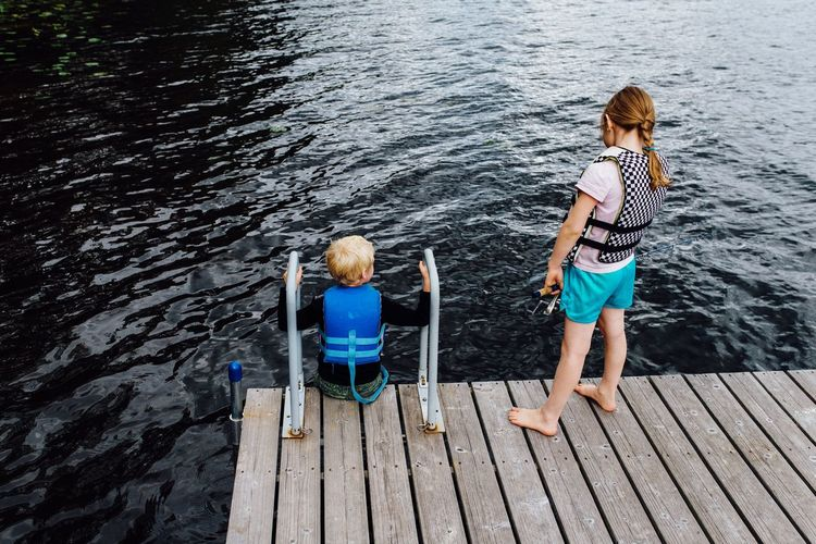 EyeEm Selects Child Childhood Boys Rear View Two People Togetherness Full Length Pier Lake High Angle View Day Wood - Material Water Elementary Age Leisure Activity Standing Girls People Outdoors Bonding Fishing