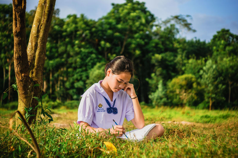 Girl studying on grassy field