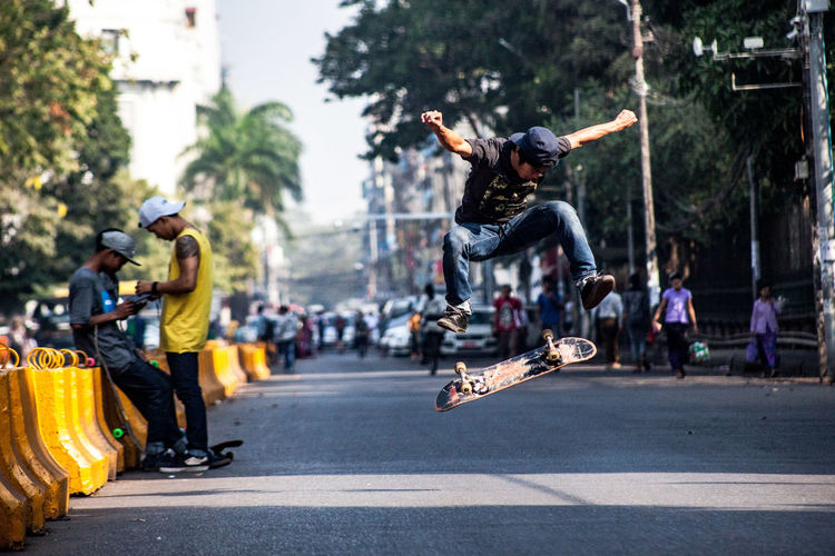 A skater doing trick on the street beside Maharbandoola Park. Yangon, Myanmar 2018 2016 Getty Images Love Madness Rangoon Skateboarding Yangon Day Full Length Hae Thaw Htet Helmet Kenji Leisure Activity Lifestyles Men Mid-air Motion Myanmar Outdoors People Real People Road Skate Skill  Street