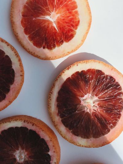 Blood orange slices in sun and shadow on a white background Food And Drink Food Fruit Healthy Eating Freshness SLICE Wellbeing Close-up Blood Orange Still Life Citrus Fruit Juicy Healthy Lifestyle Organic No People Indoors  Directly Above
