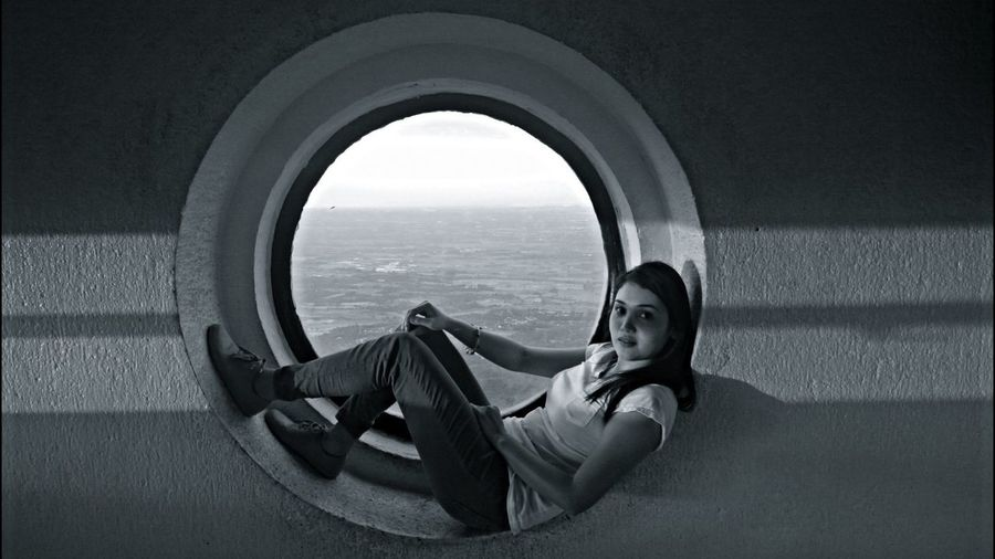 Portrait Of Woman Resting On Circular Window Against Sea