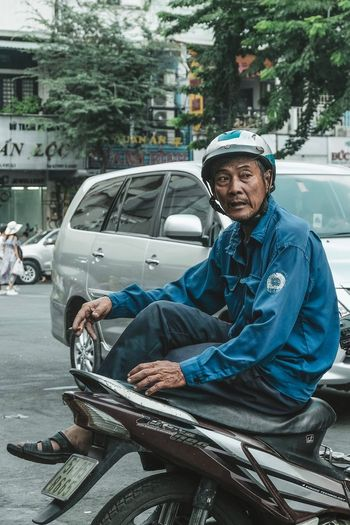 Portrait of man sitting on road in city