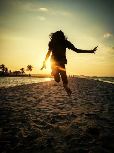 Silhouette girl jumping at beach against sky during sunset