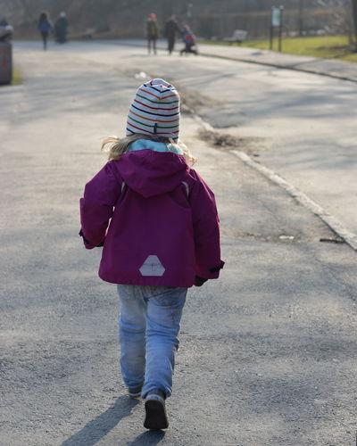 Rear View Full Length Of Girl Walking On Street