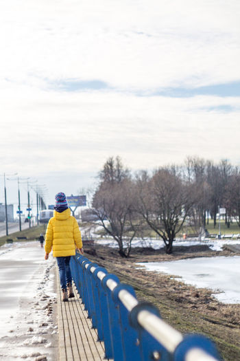 Full Length Rear View Of Person Walking On Footpath By Railing Against Sky During Winter