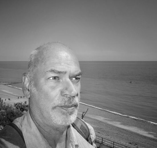 Close-Up Of Man At Beach Against Sky