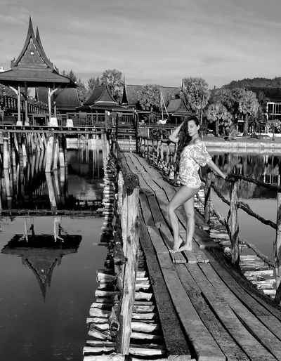 Sensual Woman Standing On Bridge Over Lake Against Houses