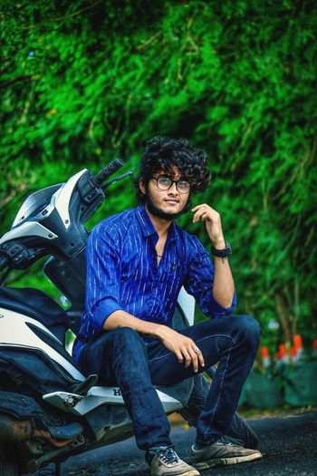 Young man sitting on motor scooter against tree