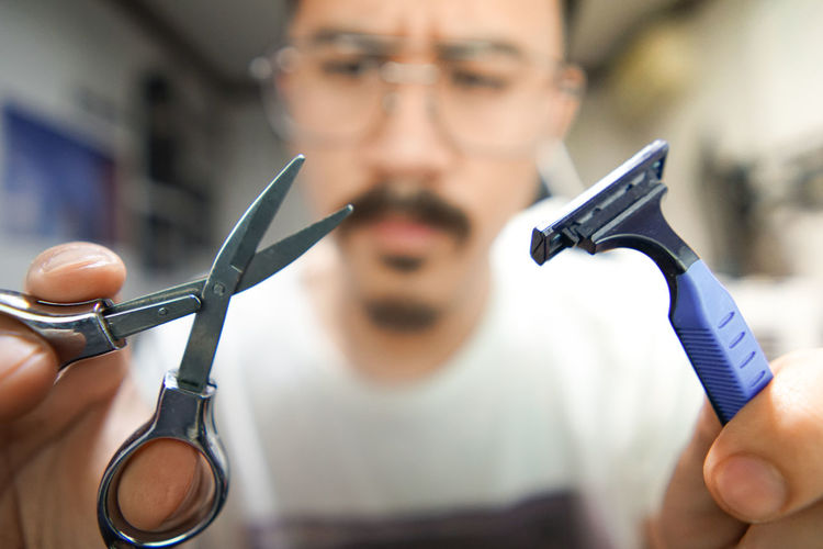 Man wearing eyeglasses holding scissors and razor at home
