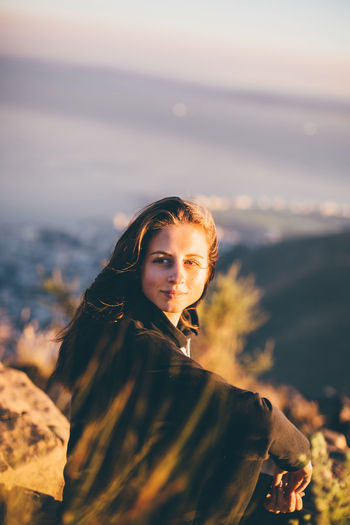 Young woman sitting on mountain against sky during sunset