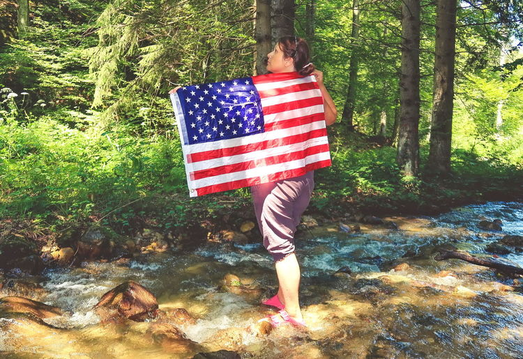 Woman holding a USA flag in the nature Water Nature Freedom Holiday Travel Spring Flag American America Vacation USA Forest Woman United States American Flag Fourth Of July 4th July Outdoor Nature Photography Environment USA FLAG United States Of America Holding Lifestyles Real People One Person Striped Leisure Activity Outdoors Women Tree