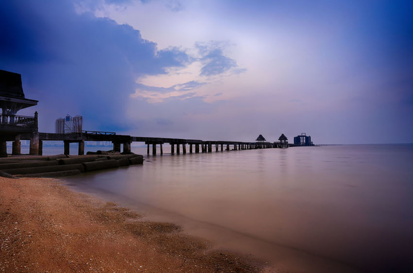 Old bridge in the sea on twilight time after sunset,nature of outdoor tropical coast in Thailand of Popular attractions the name is Wat Jit-ta-pha-wan in Chonburi province. Sky Water Cloud - Sky Sea Scenics - Nature Pier Beauty In Nature Nature Sunset Tranquil Scene Tranquility No People Beach Built Structure Architecture Horizon Over Water Land Dusk Jetty Outdoors Old Bridge Old Bridge Abandoned Bridge Old Bridges Old Bridge Vs New Bridge Twilight