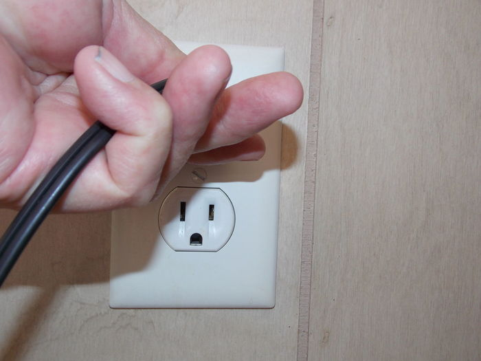 Cropped image of man connecting electrical plug in outlet