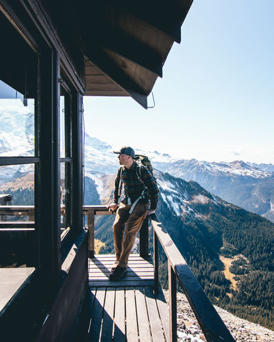 Man standing on railing by mountain against sky