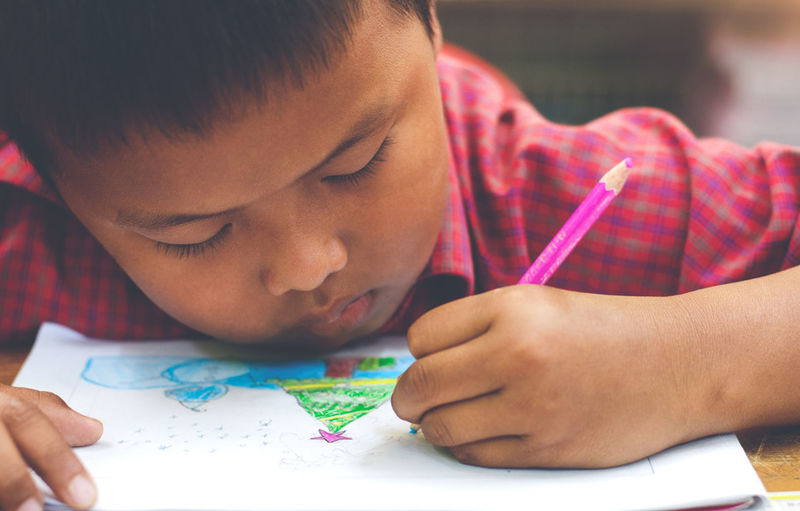 Close-up portrait of boy holding paper