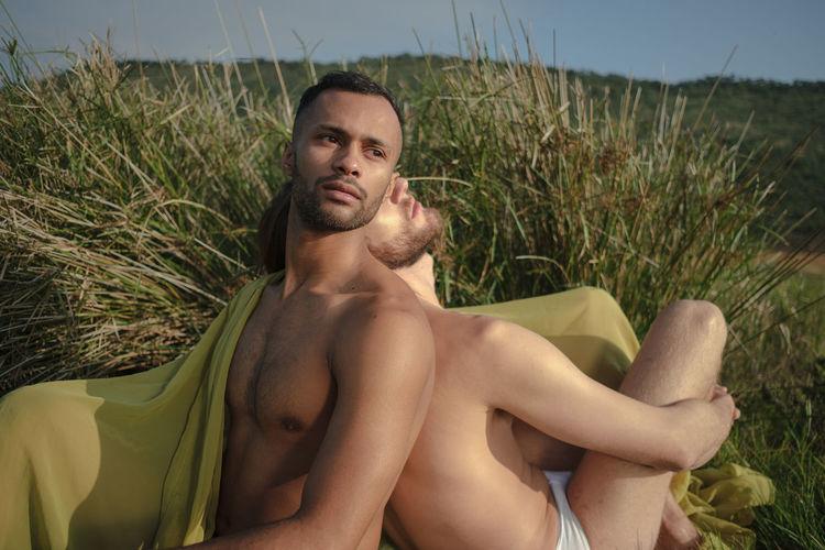 Shirtless gay men sitting back to back on land