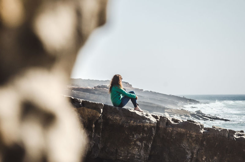 Side View Of Girl Sitting On Rocky Shore Against Clear Sky