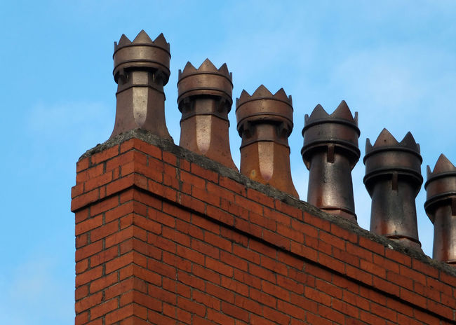 A row of old fashioned traditional clay chimney pots on a red brick support against a blue sky from when houses where built coal burning heating Chimney Roof Blue Brick Building Building Exterior Clay Day House Outdoors Roof Sky Traditional