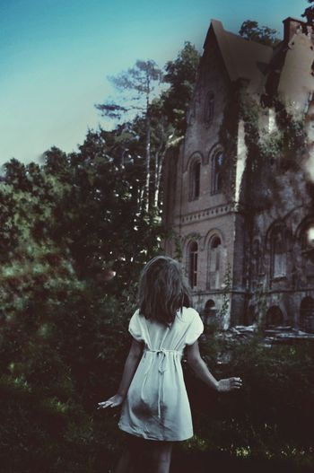Rear view of girl standing by tree and castle