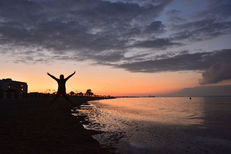 Arms Outstretched Arms Raised Baltic Sea Nature Outdoors Scenics Sea Silhouette Sky Sunset Water Breathing Space Paint The Town Yellow Connected By Travel