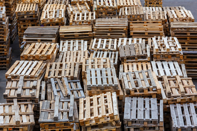 Full frame background of used wooden pallet stacks - perspective view from above