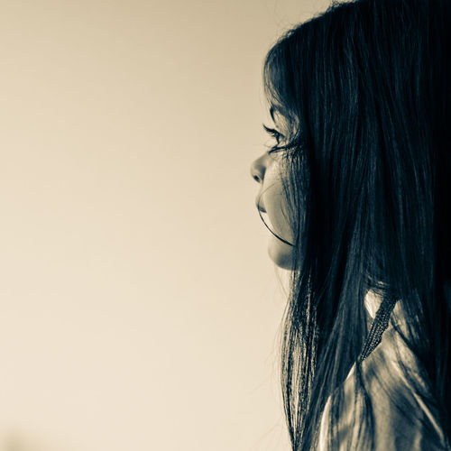 Profile View Of Girl Looking Away Against Beige Background