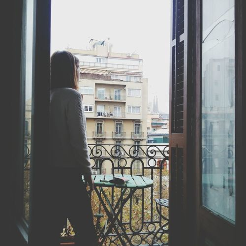 Rear View Of Woman Standing On Balcony