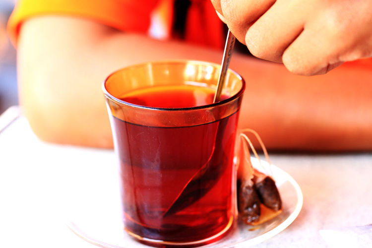 Cropped Image Of Person Stirring Herbal Tea