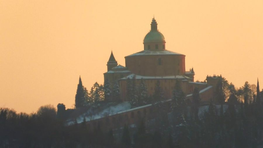 close up of San Luca basilica church with snow on Bologna hill in Italy with a flock of birds flying Bologna Bologna, Italy Italy San Luca San Luca's Church San Luca Bologna San Luca Skyline Church Cathedral Basilica Night Sunset Religion Dome Madonna Holy Mary Holy Virgin Madonna Di San Luca Dawn Snow Snowy Winter Architecture Building Exterior Built Structure Sky Place Of Worship Belief Building Spirituality Nature Clear Sky Tree No People Orange Color The Past History Travel Destinations Outdoors Spire