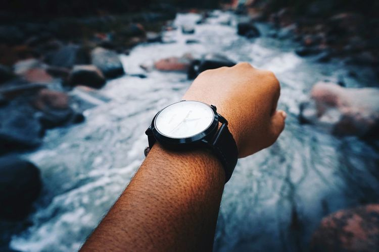 Cropped hand wearing wristwatch against river