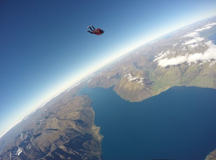 Person sky diving over mountains against