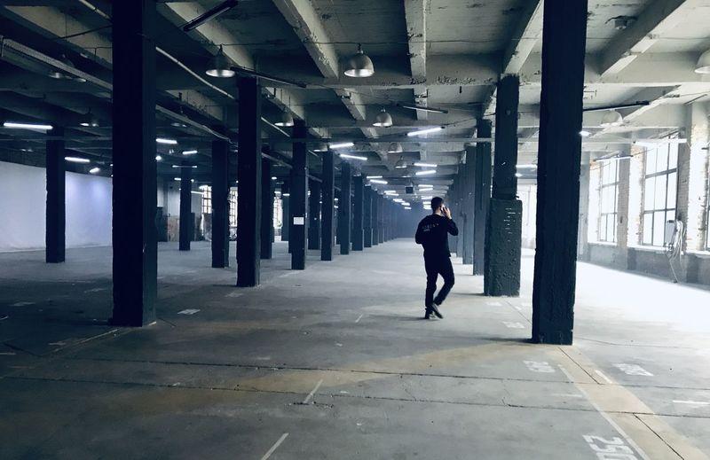 Rear view of man walking in parking lot