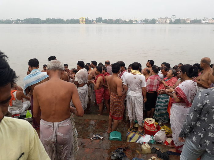 Rear view of people standing on water