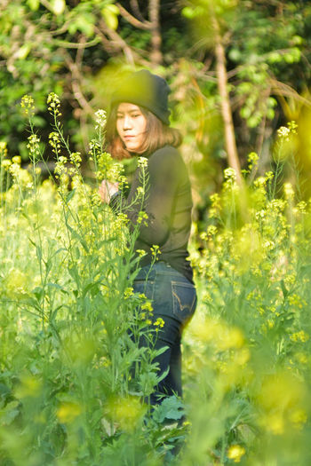 Beautiful young woman amidst plants on field