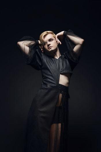 Man posing against black background