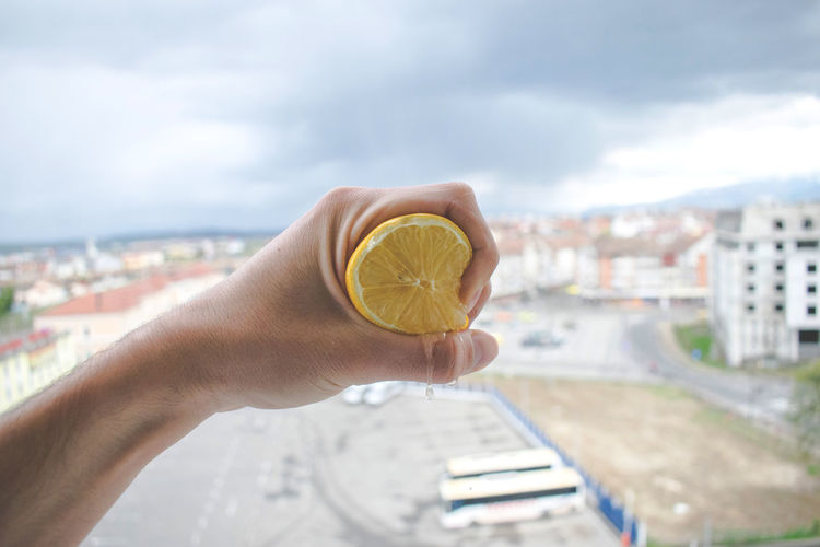 Cropped hand of man squeezing lemon against cityscape