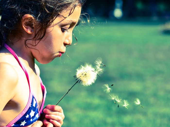 Cropped image of young girl holding and blowing a dandelion wearing bikini