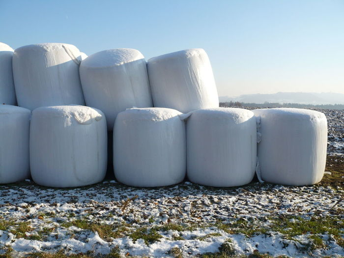 Covered Hay Bales On Farm During Winter Against Clear Sky