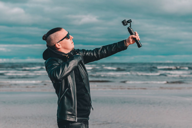 Young man wearing sunglasses filming with video camera against sea