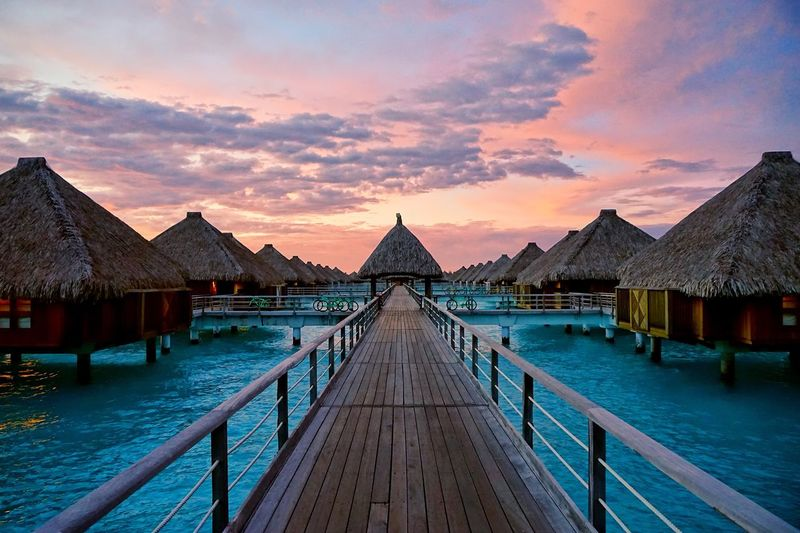 Empty Pier And Stilt Houses On Lagoon Against Sky During Sunset At Bora Bora