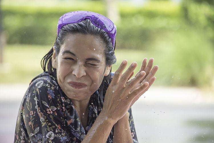 Portrait of smiling woman amidst splashing water