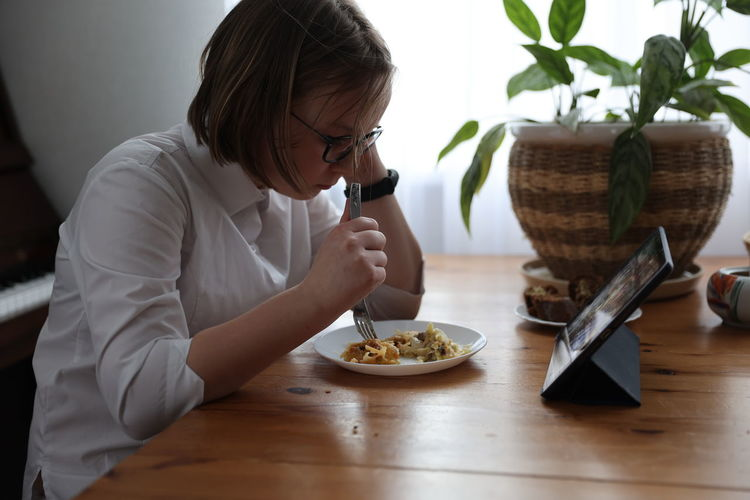 Midsection of woman holding food while sitting on table